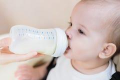 A mãe alimenta sua casa de nove meses do leite do bebê Foto de Stock Royalty Free