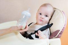 A mãe alimenta sua casa de nove meses do leite do bebê Fotos de Stock Royalty Free