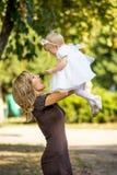 A mãe anda com a criança no jardim no verão Fotos de Stock Royalty Free
