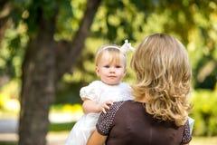 A mãe anda com a criança no jardim no verão Foto de Stock Royalty Free