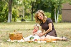 A mãe anda com a criança no jardim no verão Imagem de Stock Royalty Free