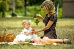 A mãe anda com a criança no jardim no verão Imagem de Stock