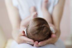 A mãe apoia a cabeça do bebê que encontra-se em seu regaço imagens de stock royalty free