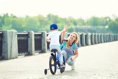 A mãe aprende seu filho pequeno montar uma bicicleta foto de stock