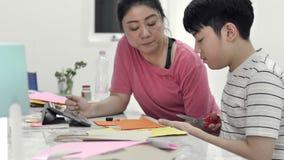 Mãe asiática Ajudando meu filho a fazer arte para mandar o professor amanhã video estoque