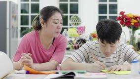Mãe asiática Ajudando meu filho a fazer arte para mandar o professor amanhã filme