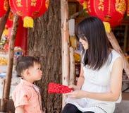 A mãe asiática dá um envelope ou um ANG-prisioneiro de guerra vermelho ao filho Foto de Stock