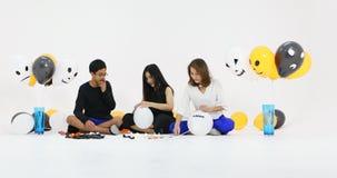 A mãe asiática da família e suas crianças juntam-se junto preparando o balão extravagante decoram para Dia das Bruxas vídeos de arquivo