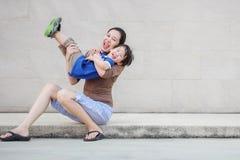 Mãe asiática do close up que guarda seu filho no movimento do divertimento em fundo textured da parede de mármore com espaço  fotos de stock