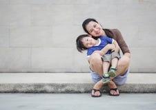 Mãe asiática do close up que guarda seu filho no movimento do divertimento em fundo textured da parede de mármore com espaço  fotografia de stock royalty free