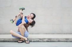 Mãe asiática do close up que guarda seu filho no movimento do divertimento em fundo textured da parede de tijolo com espaço da imagem de stock