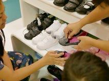 Mãe asiática e as mãos do vendedor que guardam sobre as sapatas escolhidas para sua filha pequena foto de stock