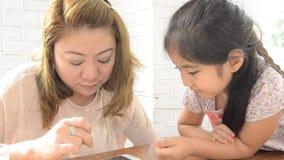 Mãe asiática e filha que jogam com telefone eletrônico vídeos de arquivo