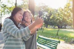 Mãe asiática e filha que tomam um selfie no parque foto de stock