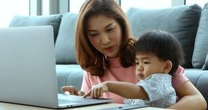 Mãe asiática e filho que sentam-se na sala de visitas, eles que usam o caderno para olhar algum vídeo video estoque