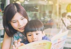 A mãe asiática está lendo seu filho um livro educacional Imagens de Stock Royalty Free