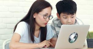 Mãe asiática feliz da família e observação e riso do filho ao olhar o portátil do computador vídeos de arquivo