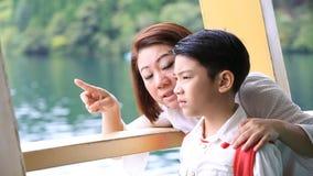 Mãe asiática nova com suporte pequeno do filho na plataforma do navio de cruzeiros filme