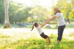 M?e asi?tica nova e filha pequena que jogam o parque com divertimento e felicidade, fam?lia para apreciar junto e relaxar e lazer foto de stock