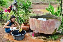 A mãe asiática nova lava pratos na cozinha primitiva imagem de stock