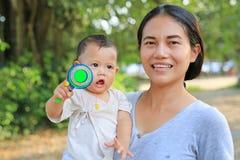 A mãe asiática nova que leva seu bebê e que joga Pongapaeng brinca o brinquedo chinês fora foto de stock
