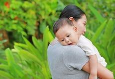 Mãe asiática que leva seu bebê infantil no jardim verde fotografia de stock royalty free