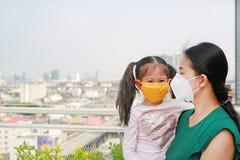 Mãe asiática que leva sua filha com vestir uma máscara da proteção contra PM 2 poluição do ar 5 na cidade de Banguecoque tailândi imagens de stock