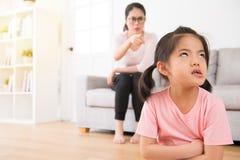 Mãe asiática que senta-se em apontar irritado do sofá fotografia de stock