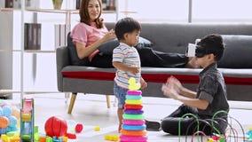 Mãe asiática que senta-se no sofá, realidade virtual do uso mais velho do filho com seu irmão mais novo na sala de visitas filme