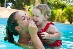 Mãe ativa nova feliz e bebê pequeno encaracolado que têm o divertimento em uma piscina fotos de stock royalty free