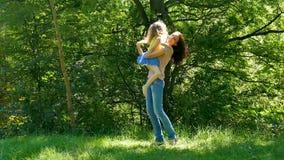 Mãe atrativa feliz na camisa cor-de-rosa e nas calças de brim que pegaram sua filha pequena no parque durante Sunny Warm Day filme