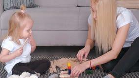 Mãe atrativa nova loura com sua filha encantador pequena que constrói uma torre dos blocos da cor filme