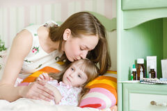 A mãe beija a criança doente Imagens de Stock