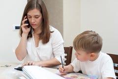 A mãe bem sucedida trabalha em casa com seu filho fotografia de stock