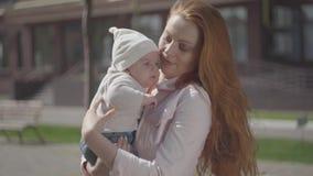 Mãe bonita bonito nova do ruivo do retrato que guarda um bebê adorável em seus braços e que fala a ele em uma mola ensolarada filme