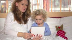Mãe bonita com a menina bonito pequena da filha que joga o jogo no tablet pc video estoque