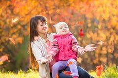 Mãe bonita com menina da criança fora no parque do outono foto de stock