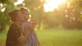 Mãe bonita com sua filha na natureza que faz bolhas e riso de sabão