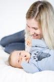 Mãe bonita e bebê que encontram-se na cama na sala de criança Fotografia de Stock Royalty Free