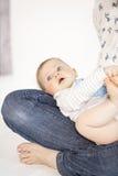 Mãe bonita e bebê que encontram-se na cama na sala de criança Imagens de Stock Royalty Free