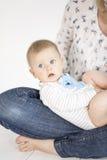 Mãe bonita e bebê que encontram-se na cama na sala de criança Imagem de Stock