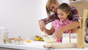 Mãe bonita e doughter novo que cozinham junto na cozinha video estoque
