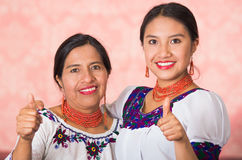 Mãe bonita e filha latino-americanos que vestem a roupa andina tradicional, abraçando ao levantar felizmente junto Fotos de Stock Royalty Free