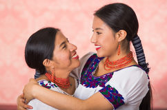 Mãe bonita e filha latino-americanos que vestem a roupa andina tradicional, abraçando ao levantar felizmente junto Imagens de Stock