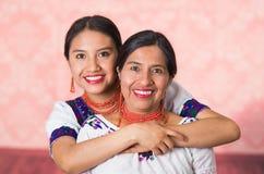 Mãe bonita e filha latino-americanos que vestem a roupa andina tradicional, abraçando ao levantar felizmente junto Fotografia de Stock Royalty Free