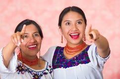 Mãe bonita e filha latino-americanos que vestem a roupa andina tradicional, abraçando ao levantar felizmente junto Imagens de Stock Royalty Free