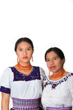Mãe bonita e filha latino-americanos que vestem a roupa andina tradicional, abraçando ao levantar junto com sério Fotografia de Stock Royalty Free
