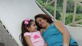 Mãe bonita e filha novas que colocam e que relaxam junto em uma rede video estoque