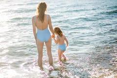 Mãe bonita e filha novas que têm o divertimento que descansa no mar Estão na água no mesmo roupa de banho, parte traseira no quad imagem de stock