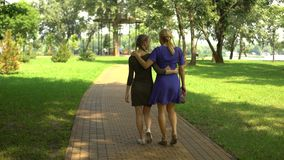 Mãe bonita e filha que andam ao longo do parque que aprecia o passatempo exterior filme